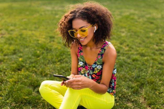 公園で楽しんでいるワイヤレスイヤホンで音楽を聴いてスマートフォンを使用して若いスタイリッシュな笑顔の黒人女性