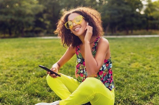 공원에서 재미 무선 이어폰에서 음악을 듣고 스마트 폰을 사용하는 젊은 세련된 웃는 흑인 여성