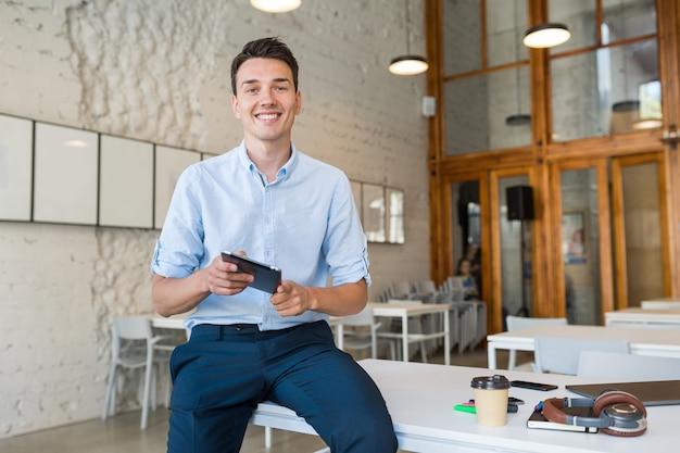 Молодой стильный улыбающийся человек в коворкинг-офисе, запускающий фрилансер, держащийся с помощью планшета