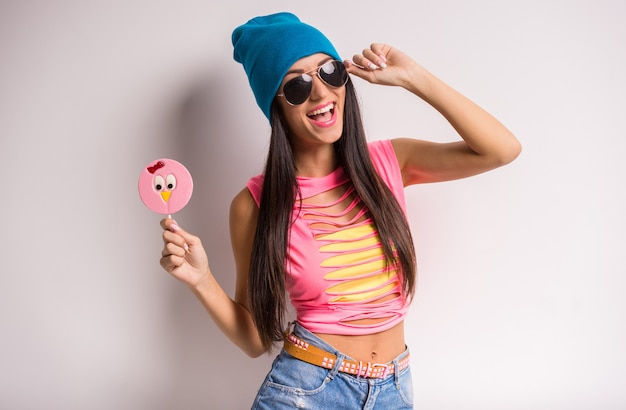 Young stylish smiling woman in blue cap and sunglasses.