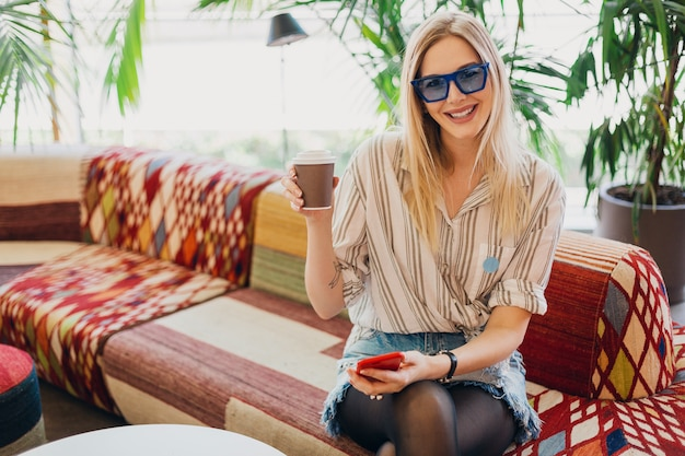 Giovane donna sorridente alla moda che si siede nel caffè hipster sul divano che indossa la camicia e occhiali da sole blu che bevono caffè