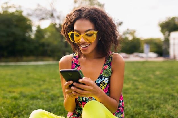 공원에서 재미 무선 이어폰에서 음악을 듣고 스마트 폰을 사용하는 젊은 세련된 웃는 여자