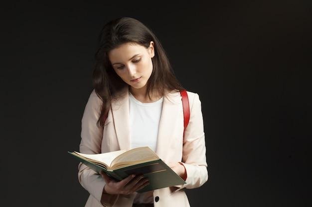 本を読んでバックパックとピンクのブレザーの若いスタイリッシュな学生女性