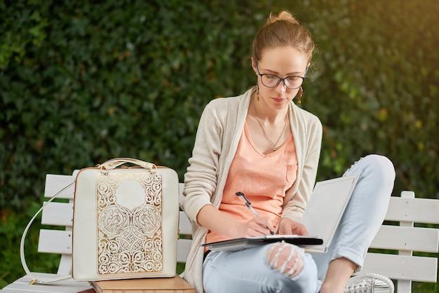 Молодой стильный студент что-то пишет на белой скамейке в парке.