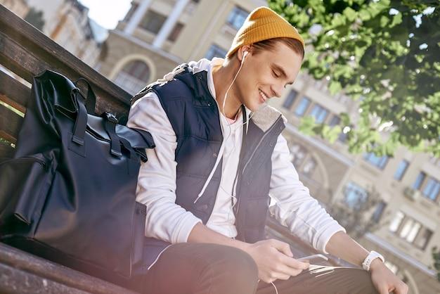 若いスタイリッシュな観光ブロガーがベンチのクローズアップで音楽を聴いています