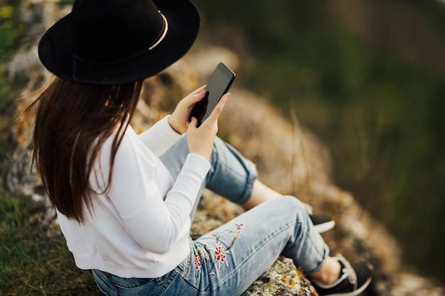 山の頂上にいて、スマートフォンで彼女の足の写真を撮ろうとしている若いスタイリッシュな旅行者