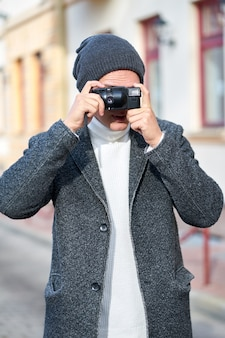 Young stylish trendy man wearing a gray coat, white sweater and gray hat with camera walking in the street and taking photos