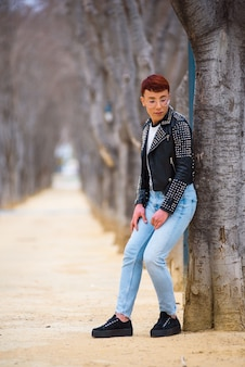 Young stylish weared gay man posing in a park