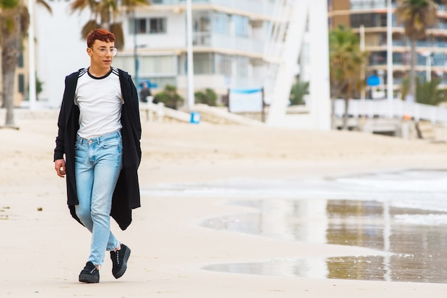 Young stylish weared man walking on a beach