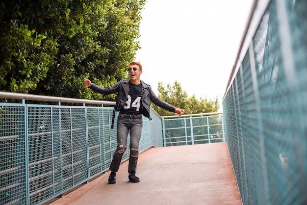 Young stylish wearing boy jumping on a bridge