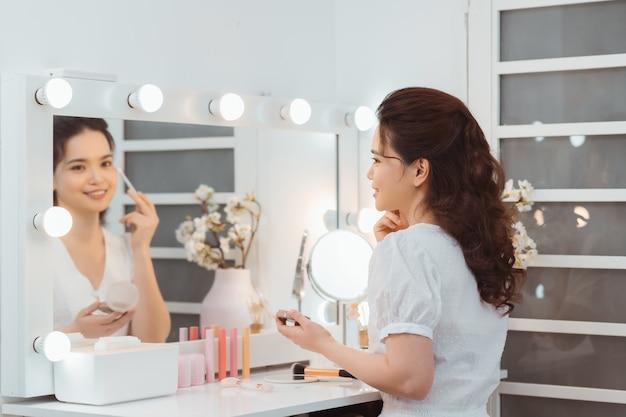 ミラーのアイシャドウブラシで化粧を適用する若いスタイリッシュな女性
