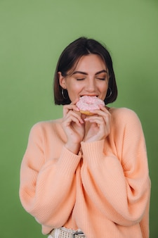 Giovane donna alla moda in maglione pesca casual isolato sulla parete verde oliva con lo spazio felice della copia della ciambella rosa