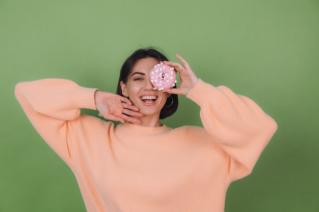 Young stylish woman in casual peach sweater  isolated on green olive wall with pink donut happy copy space