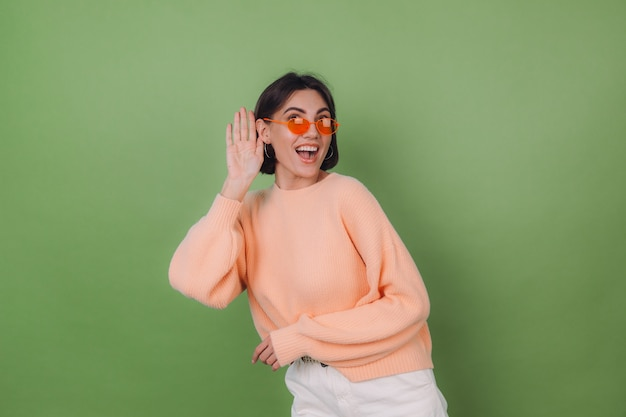 Young stylish woman in casual peach sweater and orange glasses isolated on green olive wall curious try to hear what you saying with hand by ear copy space