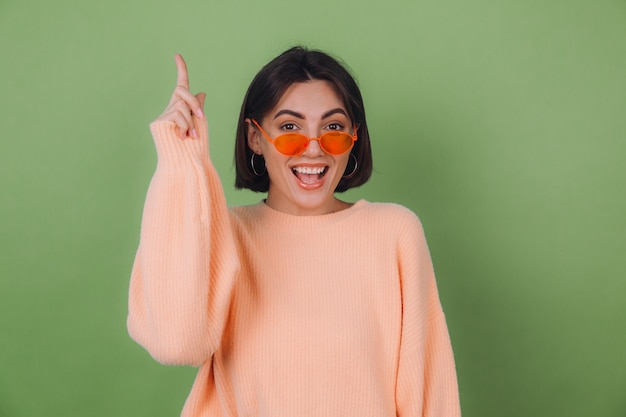 Young stylish woman in casual peach sweater and orange glasses isolated on green olive wall excited point index fingers up copy space