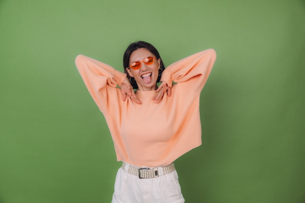 Young stylish woman in casual peach sweater and orange glasses isolated on green olive wall happy positive funny jumping around copy space