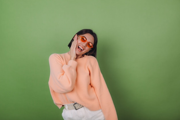 Young stylish woman in casual peach sweater and orange glasses isolated on green olive wall happy positive smiling laugh around copy space
