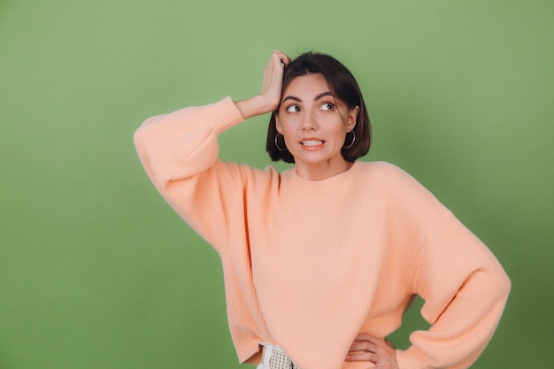 Young stylish woman in casual peach sweater and orange glasses isolated on green olive wall preoccupied put hand on head look aside copy space