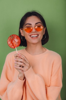 Young stylish woman in casual peach sweater and orange glasses isolated on green olive wall with orange lollipop positive smile copy space