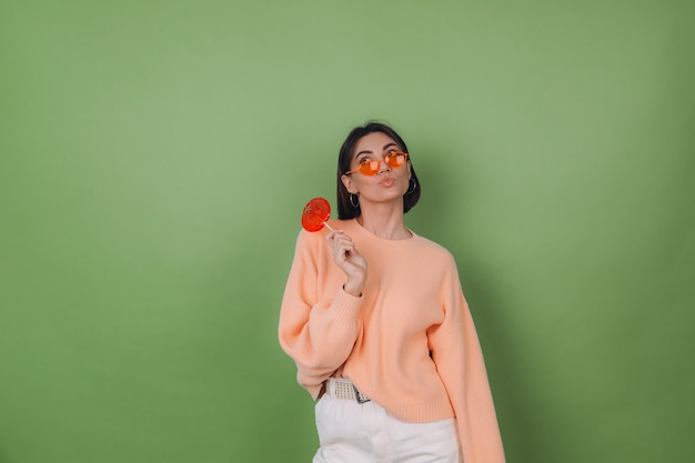Young stylish woman in casual peach sweater and orange glasses isolated on green olive wall with orange lollipop thoughtful look aside thinking copy space
