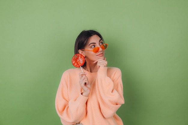 Giovane donna alla moda in maglione pesca casual e occhiali arancioni isolati sul muro verde oliva con lecca-lecca arancione sguardo premuroso da parte il pensiero spazio di copia