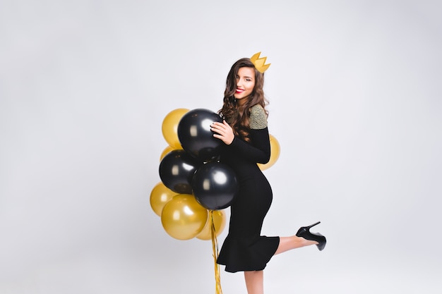 Young stylish woman celebrating new year, wearing black dress and yellow crown, happy carnival disco party, sparkling confetti, holding yellow and black balloons, having fun.
