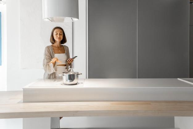 현대 부엌에서 인덕션 호브에서 요리하는 젊은 세련된 여성. 주방 가전의 스마트 기술 개념