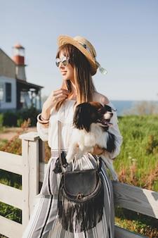 Giovane donna alla moda in campagna, tenendo in mano un cane, buon umore positivo, estate, cappello di paglia, vestito in stile bohémien, occhiali da sole, sorridente, felice, soleggiato