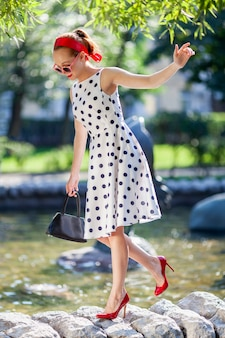 Young stylish woman in a dress and red shoes walks in the park on a sunny day.