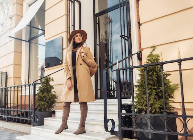 Молодая стильная женщина, одетая в пальто и фетровую шляпу. осенняя одежда. уличная мода