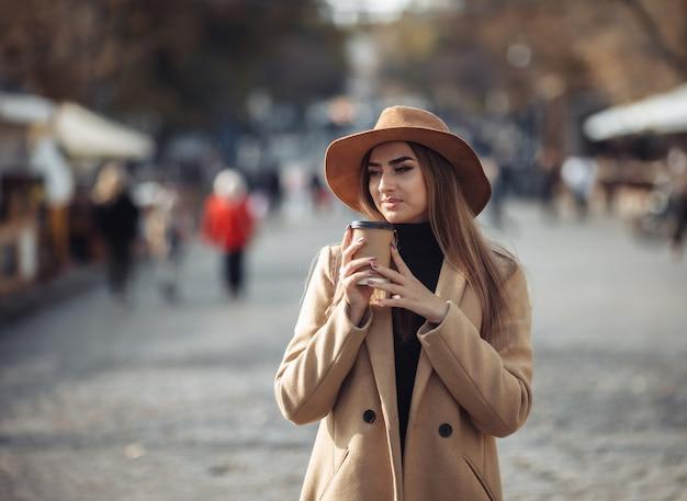 コートとフェルトの帽子をかぶったスタイリッシュな若い女性が街を歩き回り、外出先でコーヒーを飲みます。秋の時間