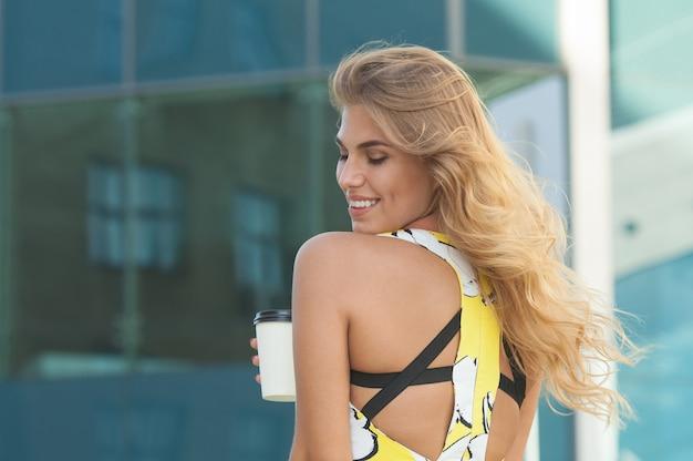街の通りに行くためにコーヒーを飲む若いスタイリッシュな女性