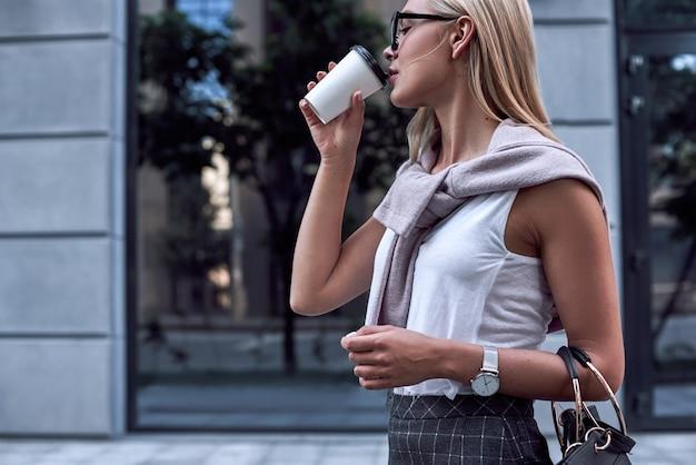 Молодая стильная женщина пьет кофе крупным планом