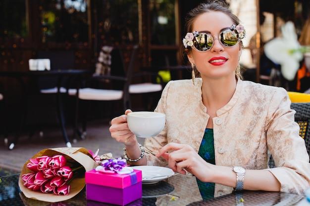 Giovane donna alla moda, occhiali da sole alla moda, seduto al caffè, che tiene tazza di cappuccino