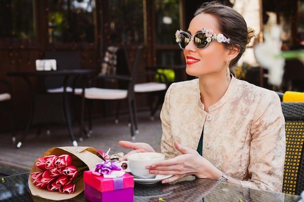 若いスタイリッシュな女性、ファッションサングラス、カフェに座って、カプチーノのカップを保持
