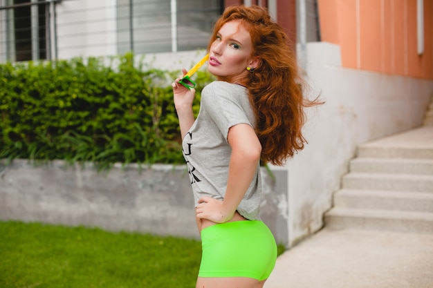 Young stylish woman in fitness apparel, ginger hair, green shorts, sunglasses, oversize t-shirt, hang over, party mood. having fun, sexy, hot, flirty, slim body, athletic,