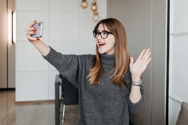 Young stylish woman in glasses waving hand saying hello to phone screen