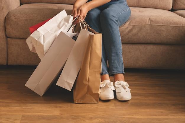쇼핑백을 들고 소파에 앉아 젊은 세련된 여자