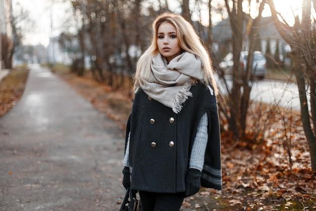 가죽 유행 가방 회색 니트 스웨터에 베이지 색 스카프와 세련 된 청바지에 검은 장갑에 빈티지 코트에 젊은 세련 된 여자 는가 나무 근처 거리에 선다. 멋진 소녀.