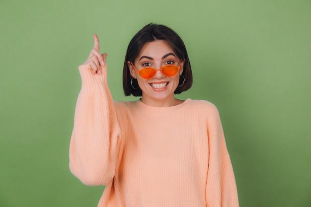 緑のオリーブの壁に隔離されたカジュアルな桃のセーターとオレンジ色のメガネの若いスタイリッシュな女性は、コピースペースを指で興奮したポイントインデックス