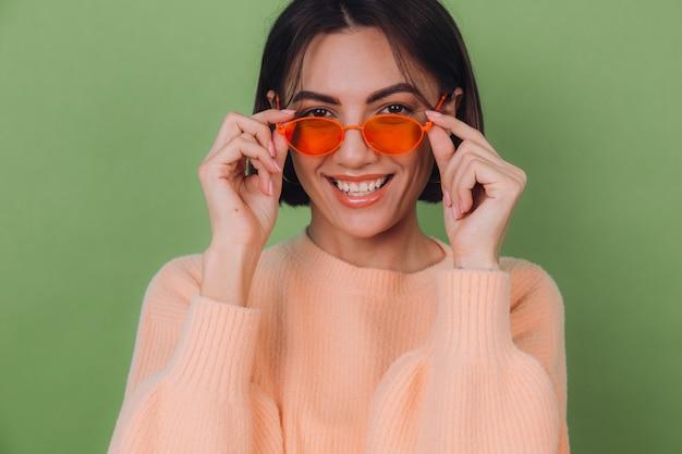 緑のオリーブの壁に分離されたカジュアルな桃のセーターとオレンジ色のメガネの若いスタイリッシュな女性