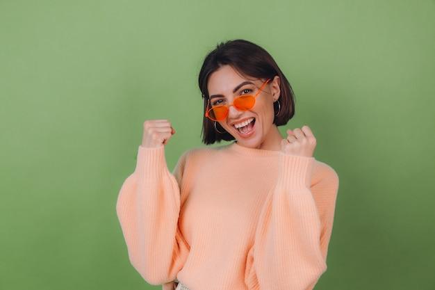 カジュアルな桃のセーターとオレンジ色のメガネで若いスタイリッシュな女性は、拳のコピースペースを食いしばって勝者のジェスチャーを行うポジティブな緑のオリーブの壁に分離