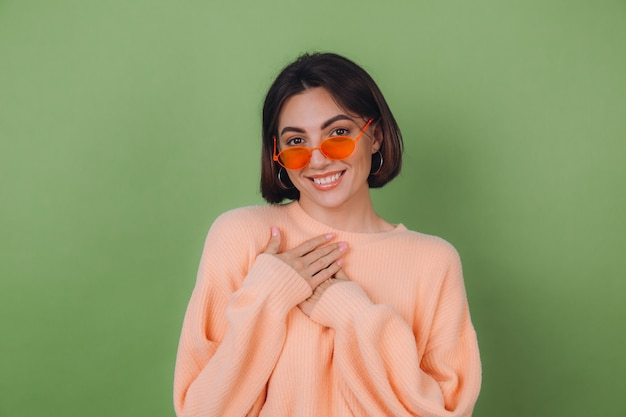 カジュアルな桃のセーターとオレンジ色のメガネの若いスタイリッシュな女性は、胸に折りたたまれた手を持って、緑のオリーブの壁、ハートのコピースペースに積極的に分離されました