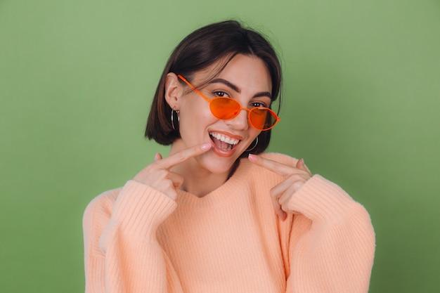 緑のオリーブの壁に分離されたカジュアルな桃のセーターとオレンジ色のメガネの若いスタイリッシュな女性人差し指で白い歯を指している肯定的な笑顔コピースペース