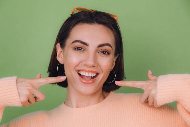 Молодая стильная женщина в повседневном персиковом свитере и оранжевых очках, изолированных на зеленой оливковой стене, позитивно улыбается, указывая на белые зубы указательными пальцами, копируя пространство