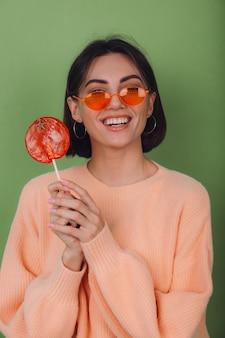 캐주얼 복숭아 스웨터와 오렌지 롤리팝 긍정적 인 미소 복사 공간 녹색 올리브 벽에 고립 된 오렌지 안경에 젊은 세련된 여자