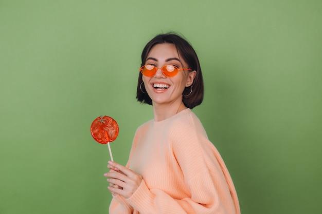 Молодая стильная женщина в повседневном персиковом свитере и оранжевых очках изолирована на зеленой оливковой стене с оранжевым леденцом на палочке позитивной улыбкой.