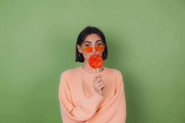 Молодая стильная женщина в повседневном персиковом свитере и оранжевых очках изолирована на зеленой оливковой стене с оранжевым леденцом на палочке, отправляя воздушный поцелуй копией пространства