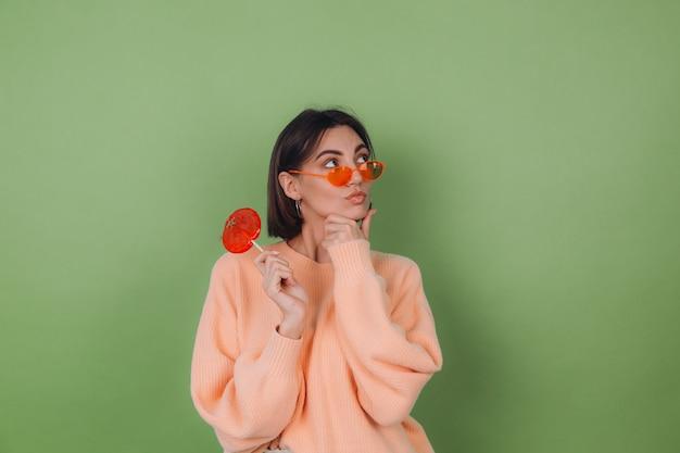 캐주얼 복숭아 스웨터와 오렌지 롤리팝 사려 깊은 표정으로 녹색 올리브 벽에 고립 된 오렌지 안경에 젊은 세련 된 여자 옆으로 생각 복사 공간