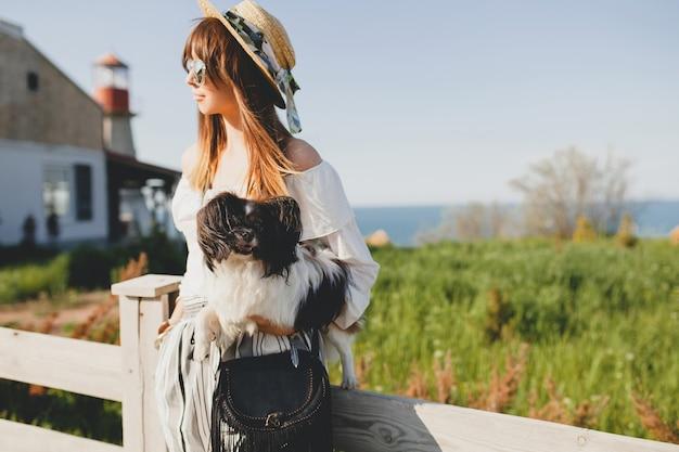 Молодая стильная женщина в сельской местности, держа собаку, счастливое позитивное настроение, лето, соломенную шляпу, наряд в богемном стиле, солнцезащитные очки, улыбается, счастливый, солнечный